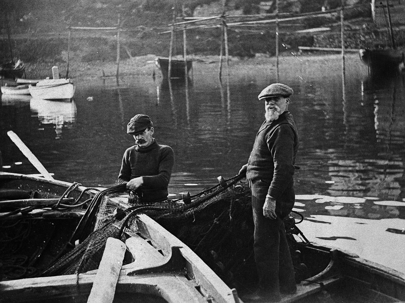 Two men transferring a ringnet into a small boat, Tarbert, 1912.