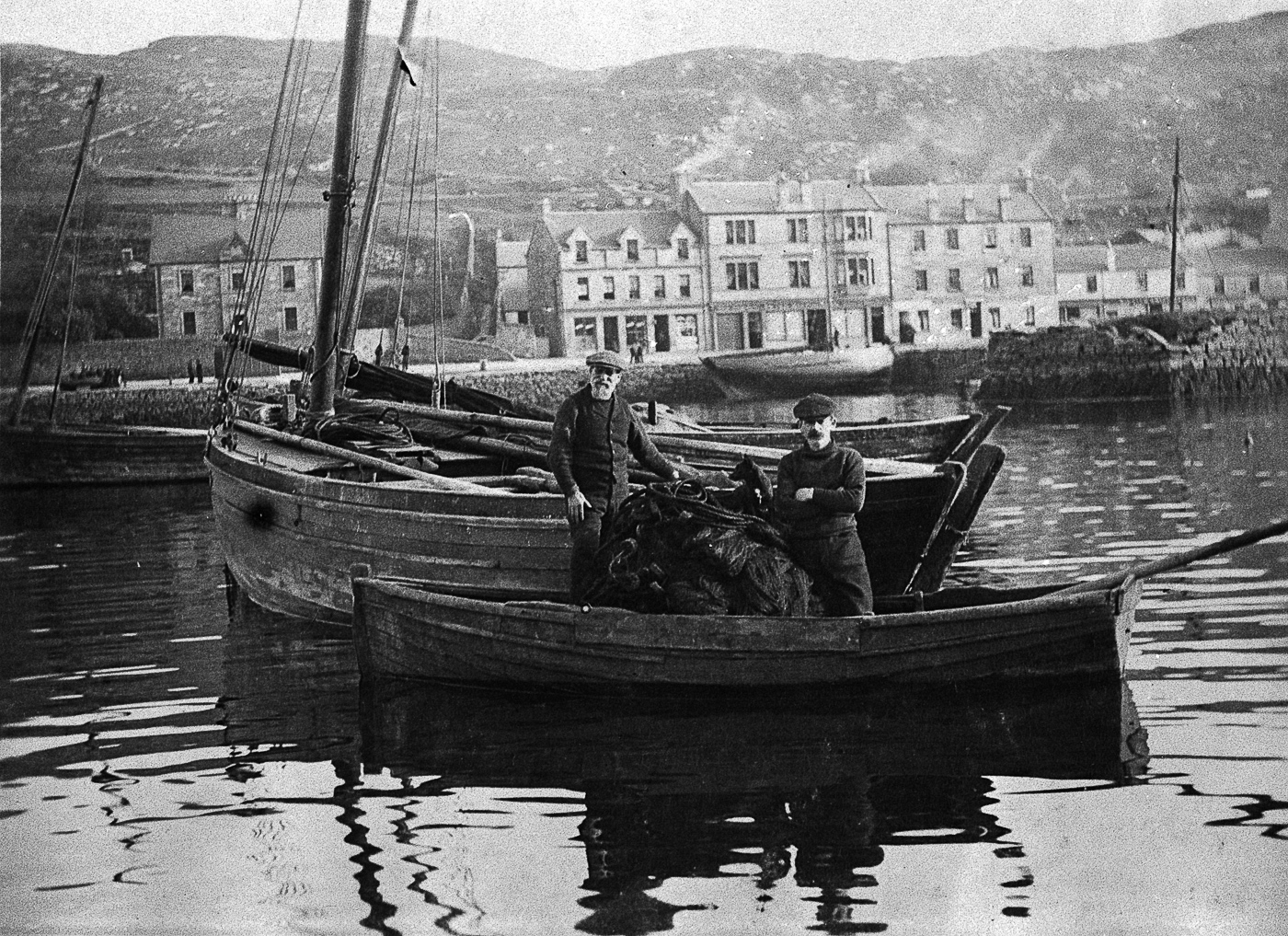 Two men transferring a ringnet into a small boat, Tarbert, 1912. L-R: Duncan Blair, unknown. Duncan Blair is grandfather to Cecil Finn.