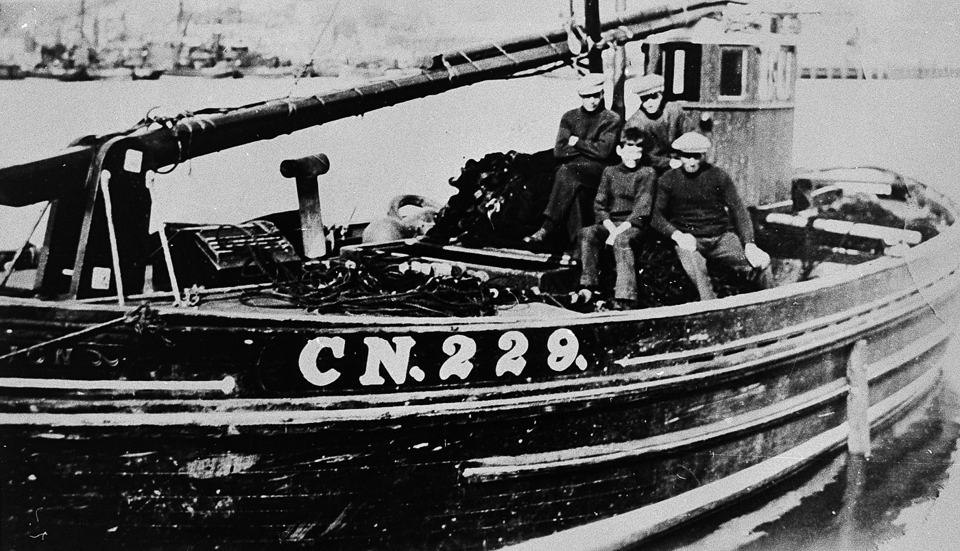 Crew onboard 'Bengullion', CN229. Campbeltown. This boat was crewed by the Blair family of Campbeltown. Back row, L-R: Willy Blair, Sandy Blair Front row, L-R: 'Young Dougal', unknown - possibly Archie or Malcom Blair, who were twins.