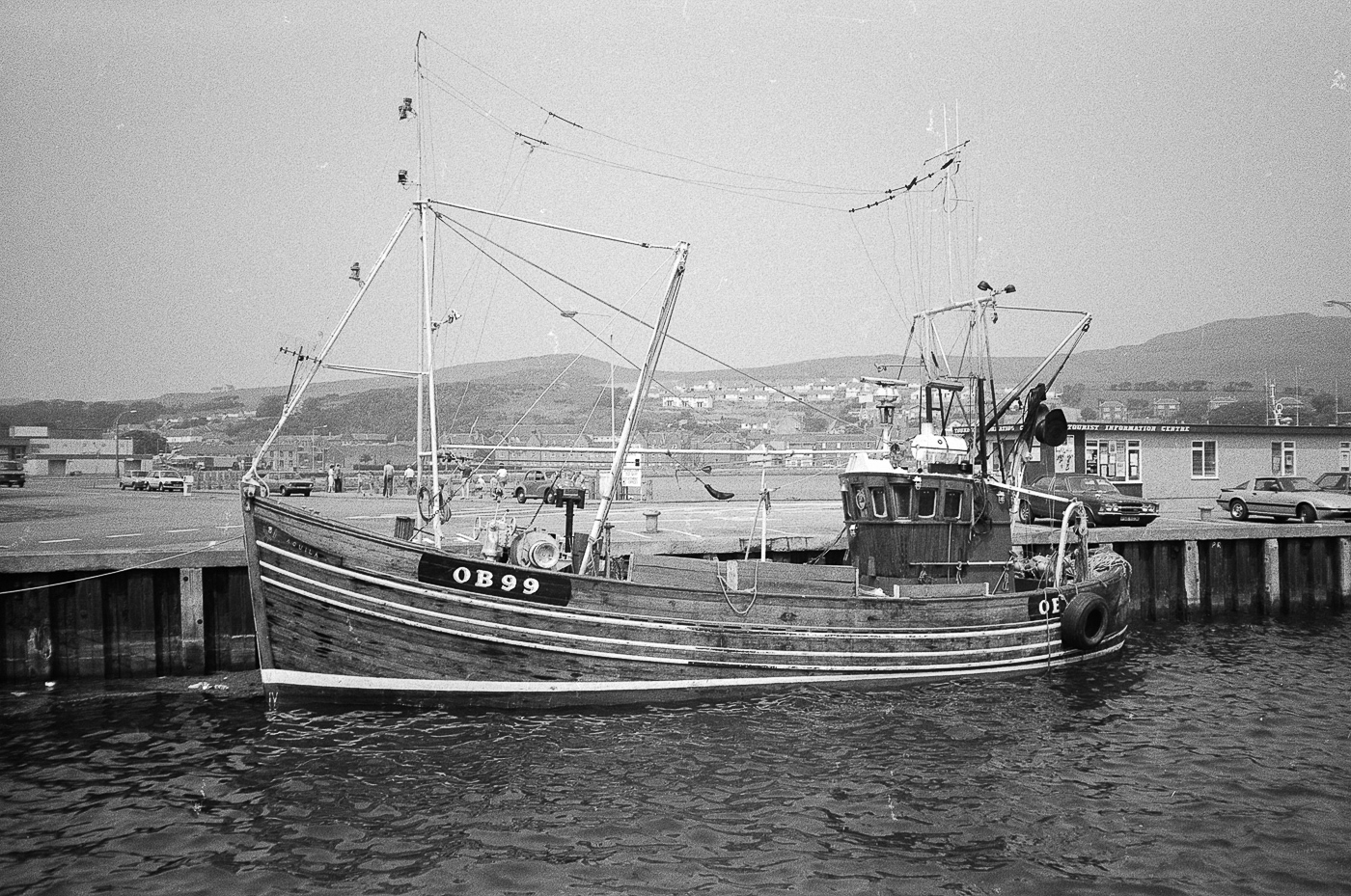Dual purpose ringnetter and trawler 'Aquila', OB99, in harbour, Campbeltown, 1983. 'Acquila', OB99, was built in Girvan in 1972. She had a varnished hull, light blue steelwork, and a varnished wheelhuse. She was later rigged out for pair trawling and in February 1986, she was sold to Pittenweem.